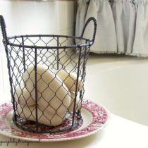 Red transferware, wire basket with lavender scented soaps add that French feel to my $100 master bathroom makeover.
