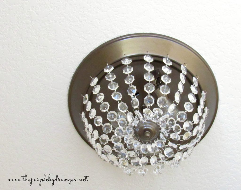 We gave the dreaded boob light a makeover as part of my $100 master bathroom makeover.