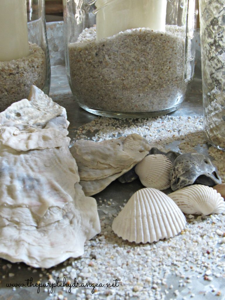 Sand, seashells, and mason jars. Summer simplicity at it's best. This mason jar candle is too easy to make.